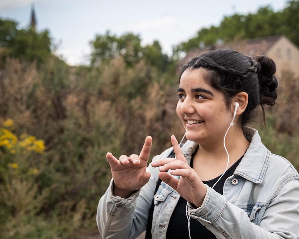 Die 14-jährige Kram steht draußen in der Natur, hat ipod-koshörer im Ohr und spielt in der Luft mit ihren Fingern Klavier.