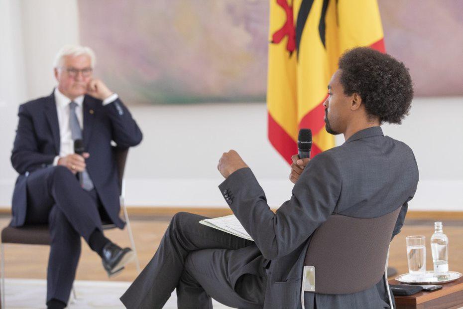 Der Vorstand des Empowerment-Vereins Each One Teach One Daniel Gyamerah sitzt Bundespräsident Frank-Walter Steinmeier auf einem Stuhl mit einem Mikrofon in der Hand und einem Zettel auf dem Schoß gegenüber.