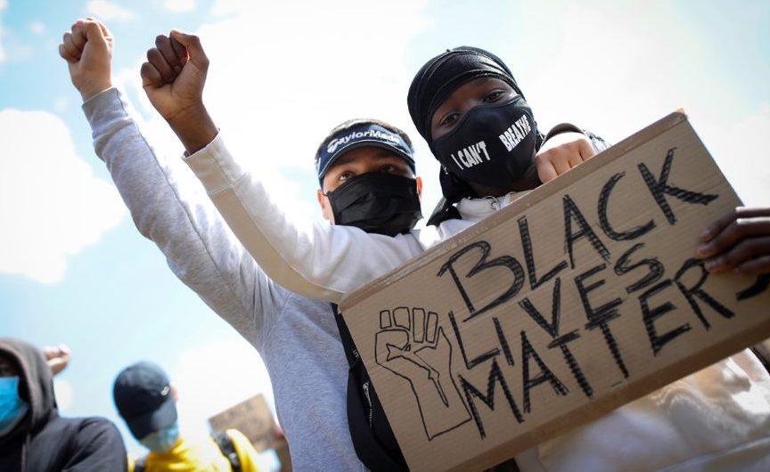 """Zwei schwarze Jungen stehen hintereinander und halten zusammen ein Pappschild mit der Aufschrift """"Black Life Matter"""" vor die Brust des vorderen Jungen. Beide strecken ihre rechte Hand zu einer Faust nach oben."""