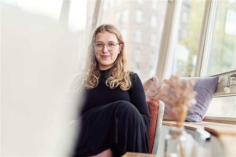 Die EU-Kompakt-Kurs-Trainerin Luisa Hieckel sitzt auf einem Stuhl an einer Fensterfront.