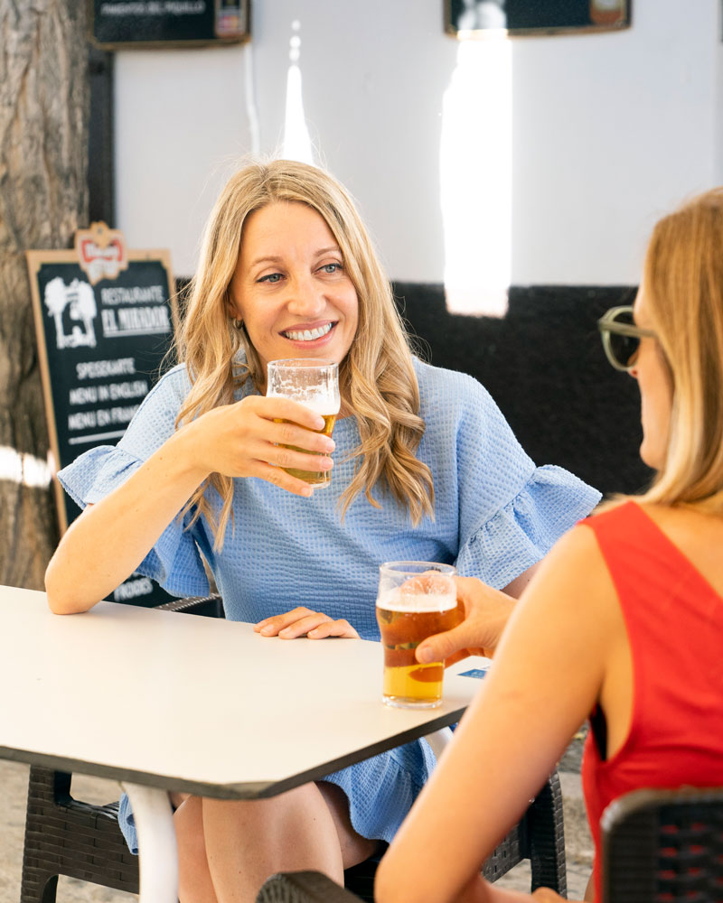 Maya Hennerkes sitzt mit einer anderen Person im roten Top an einem Tisch in eine Bar und trinkt Bier aus einem Glas.