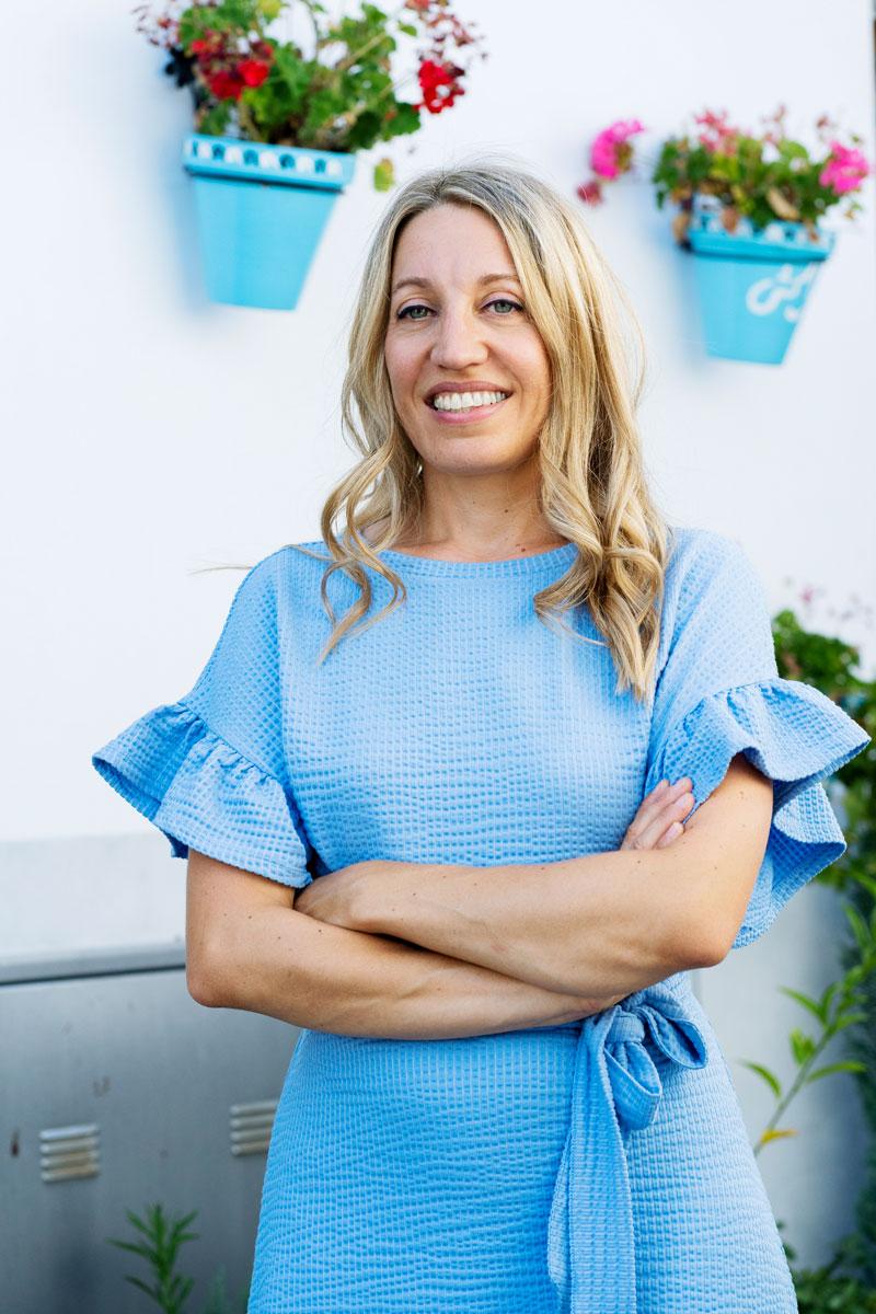 Maya Hennerkes steht in einem blauen Kleid und mit verschränkten Armen vor einer weißen Wand mit hängenden Blumentöpfen.