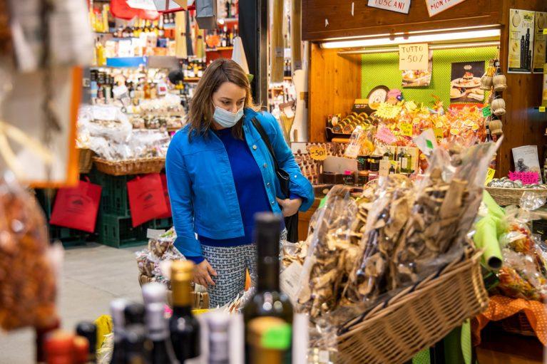 Frau (Márta Pardavi) mit Maske kauft auf Markt ein