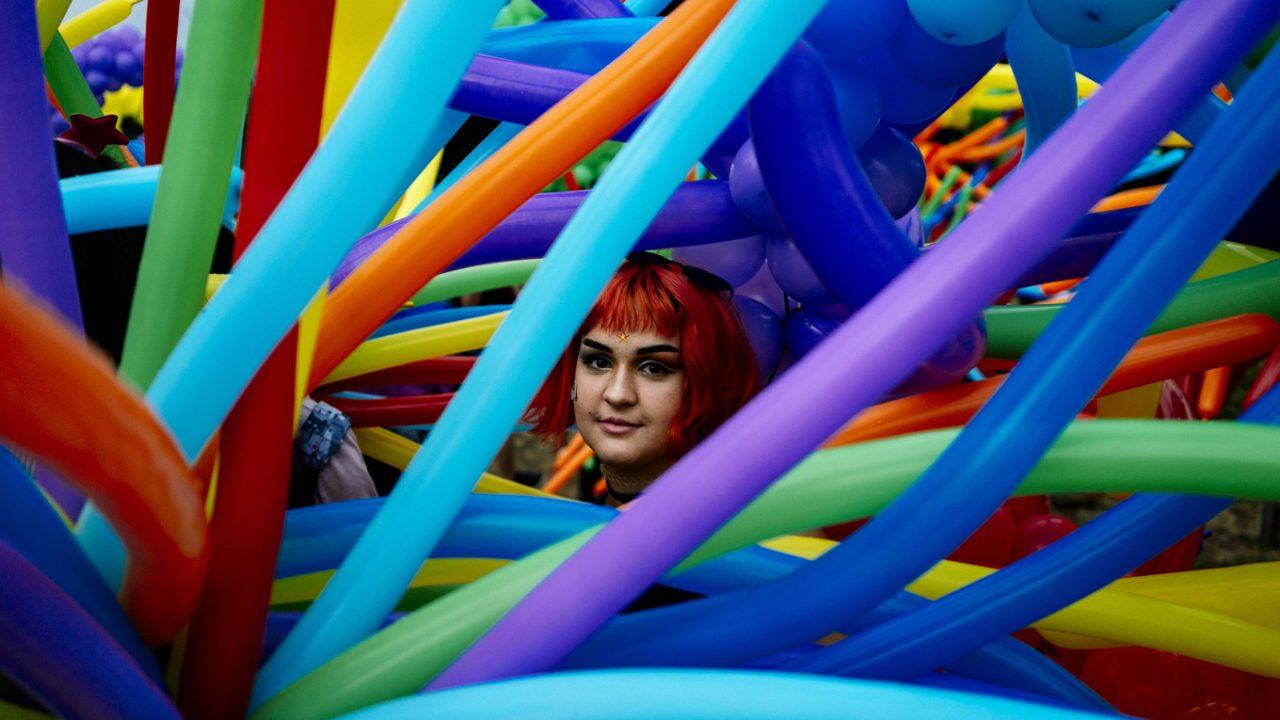 Frau umhüllt von Ballon in Regenborgnfarben