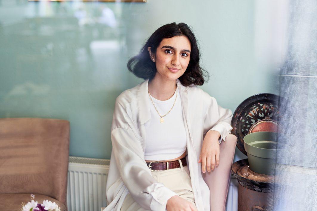 Silan sitzt in einem Café